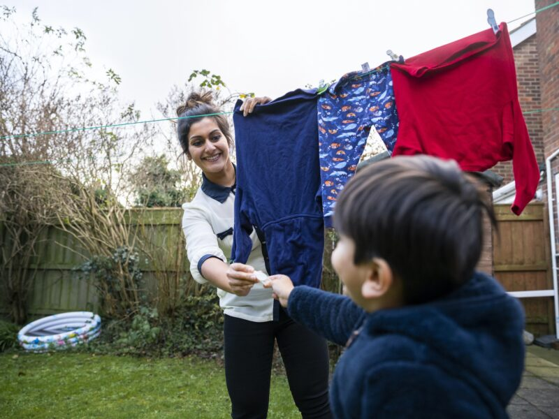 A close-up shot of a cheerful woman hanging laundry on the washing line in the garden, her young son is helping her.
