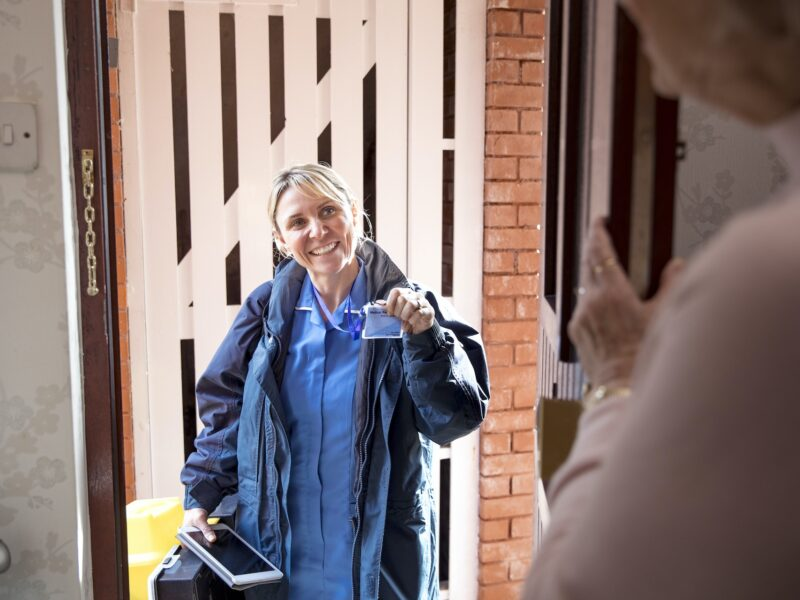 Female nurse standing in the doorway showing her identity card to an old lady opening her door.